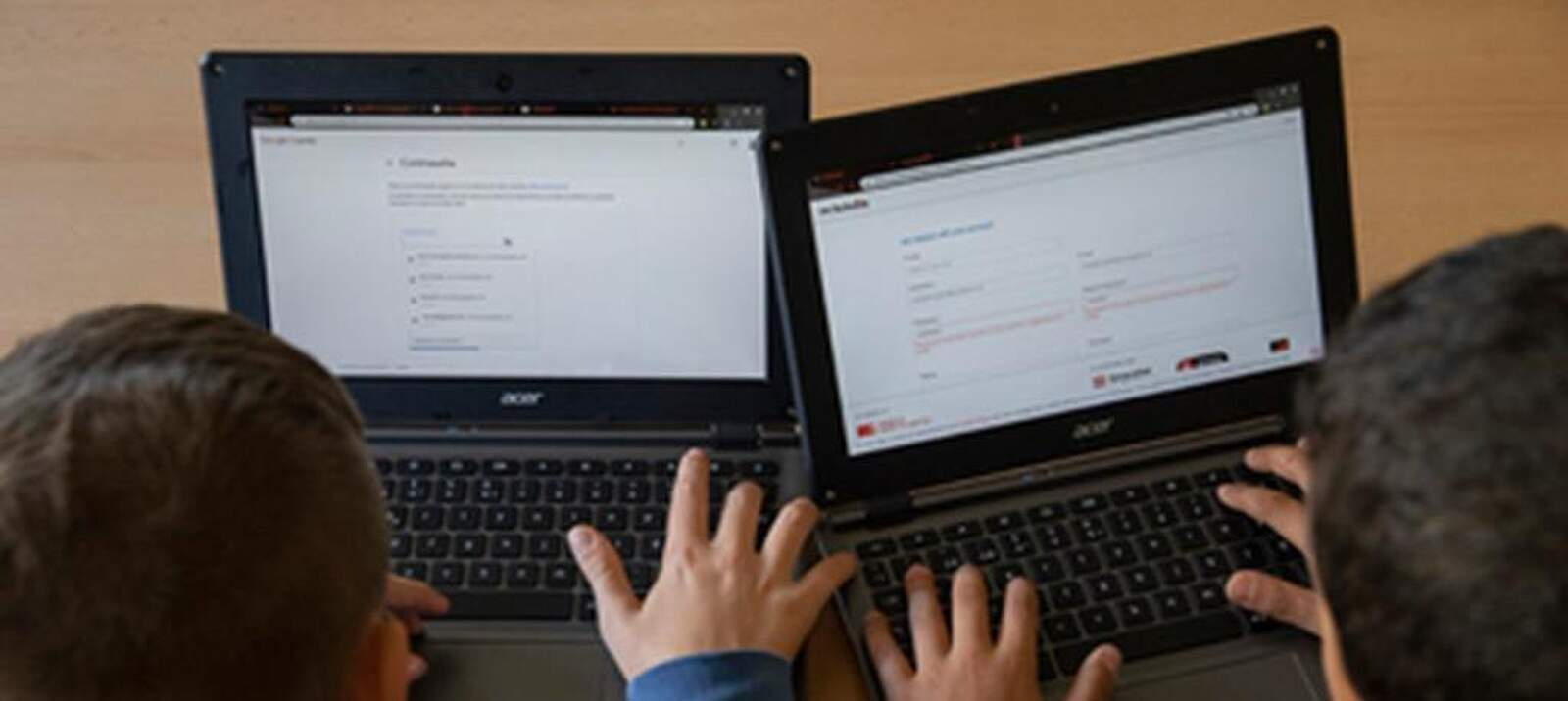 Dos escolars treballant amb ordinadors, eines bàsiques en aquest últim tram del curs