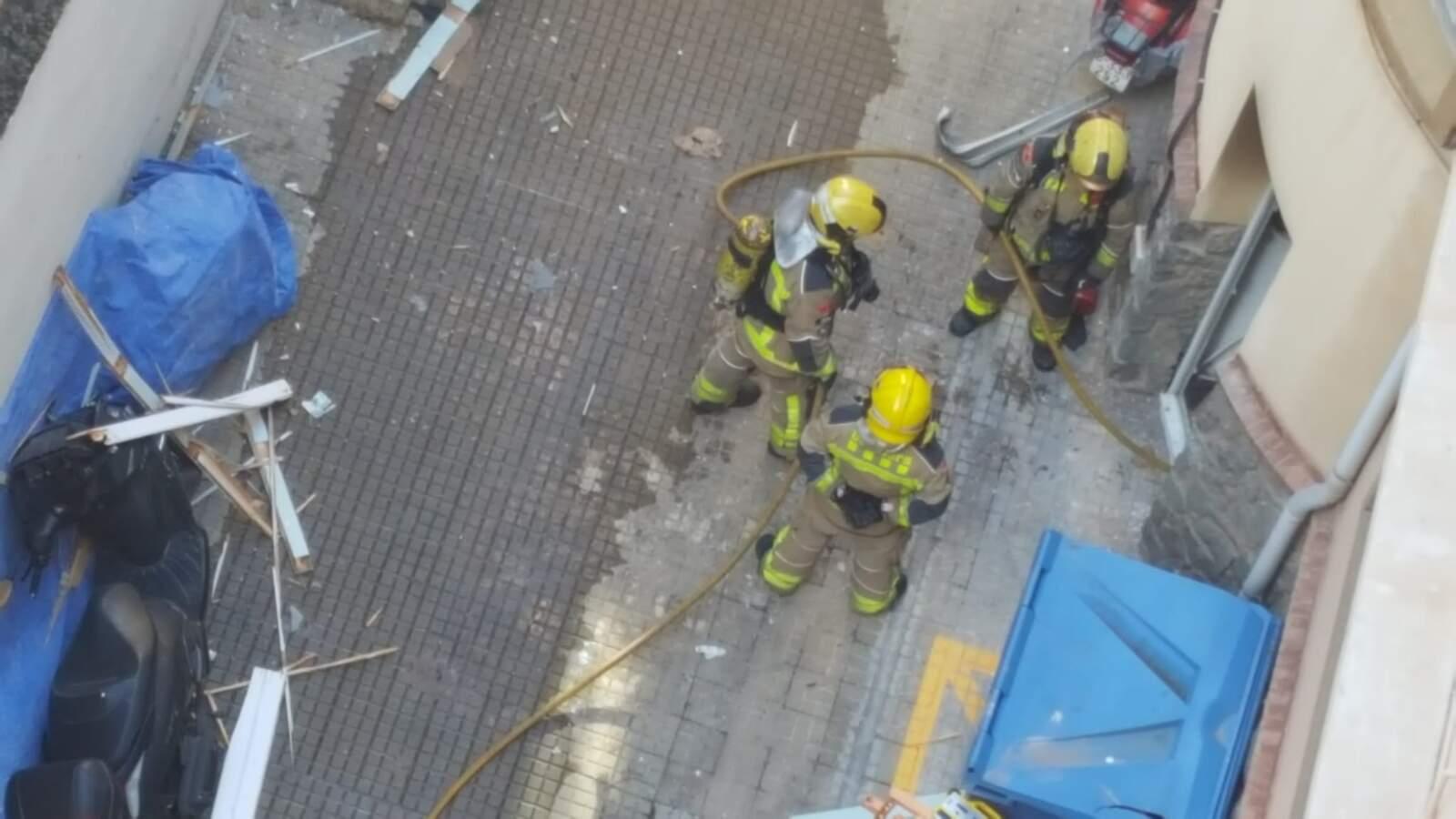 Bombers treballant en l'extinció del foc i la revisió de l'estructura