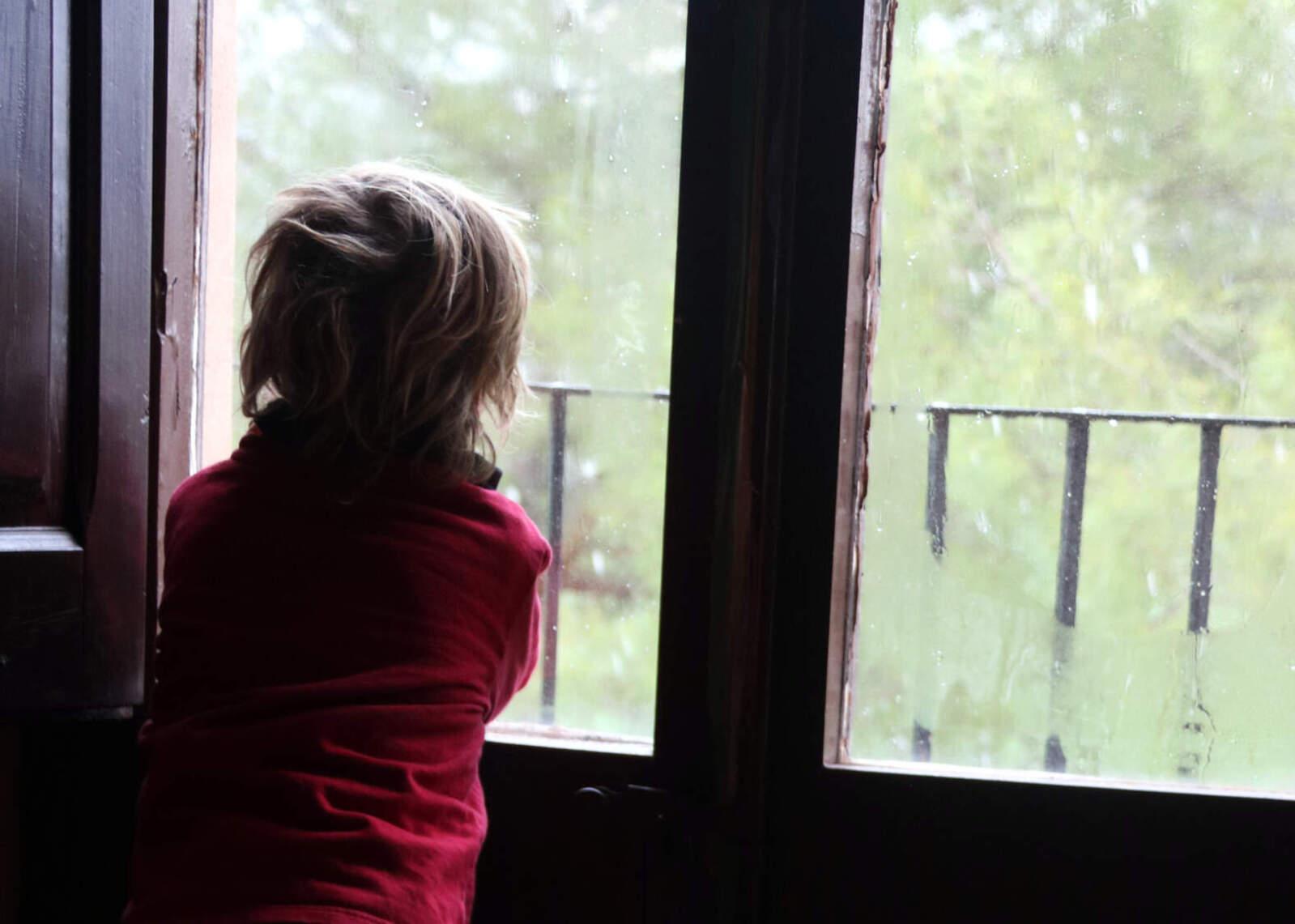 Un nen observa les volves de neu des de la finestra de casa