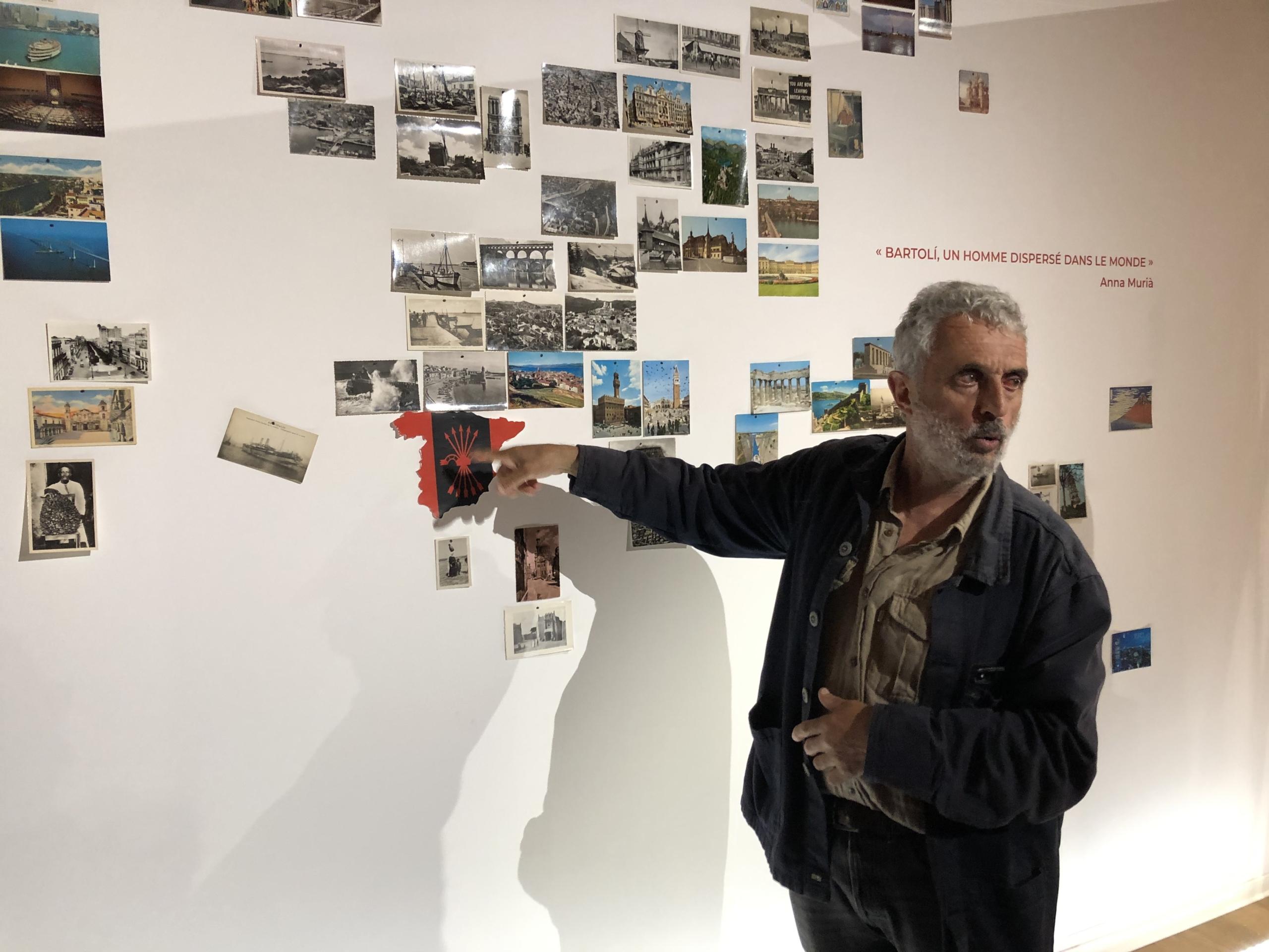 El nebot del Josep Bartolí, Jordi Bartolí, assenyalant un mural de postals del seu oncle arreu del món, menys l'Espanya franquista, a l'exposició 'Els colors de l'exili' del Memorial de Ribesaltes, amb una cita de l'Anna Murià de fons